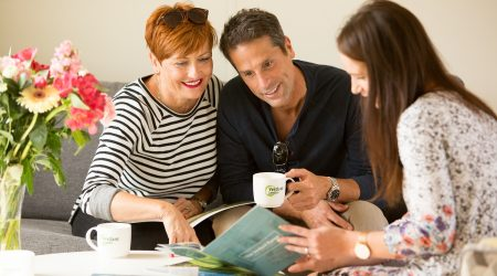 Couple with sales team member discussing holiday home ownership