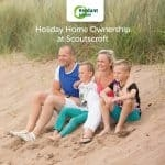 Family enjoying the beach on the front of the Scoutscroft Holiday Home Ownership vrochure cover